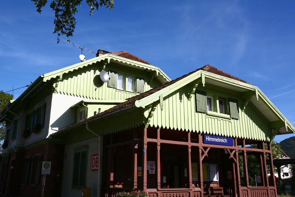 Unser schönes denkmalgeschütztes Bahnhofsgebäude. Im Erdgeschoss der Eingang zum Bahnhof mit einem überdachten Wartebereich, im oberen Teil Holverkleidung und Holzgibel, mindgrün gestrichen und grüne Fensterläden.
