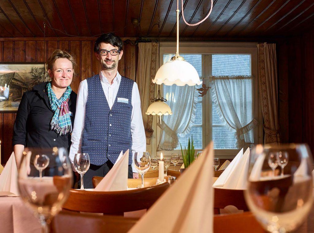 Der Innenraum des Restaurant. Die Tische sind festlich gedeckt. Die Assistenz der Geschäftsführung und ein Kellner lachen in die Kamera.