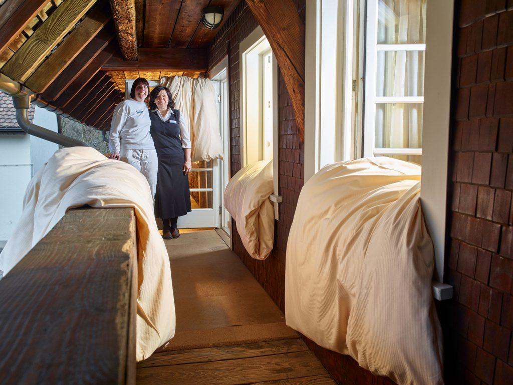 Zwei Mitarbeiterinnen stehen auf dem Balkon des Hofguts. Alte Balken, ein überhängendes Dach, die Fenster zu den Hotelzimmern stehen offen, über den Fensterbänken und der Balkonbrüstung hängen frisch bezogene weiße Bettcken, aus den Fenstern strahlt warmes Licht.