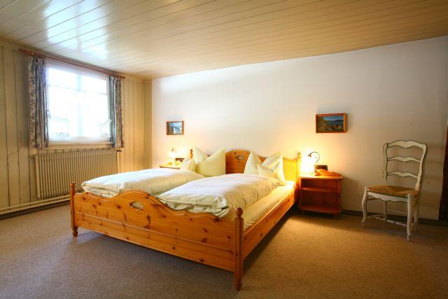 Doppelzimmer einfach: Ein Doppelbett aus Holz, gedämpftes Licht, Gardinen am Fenster