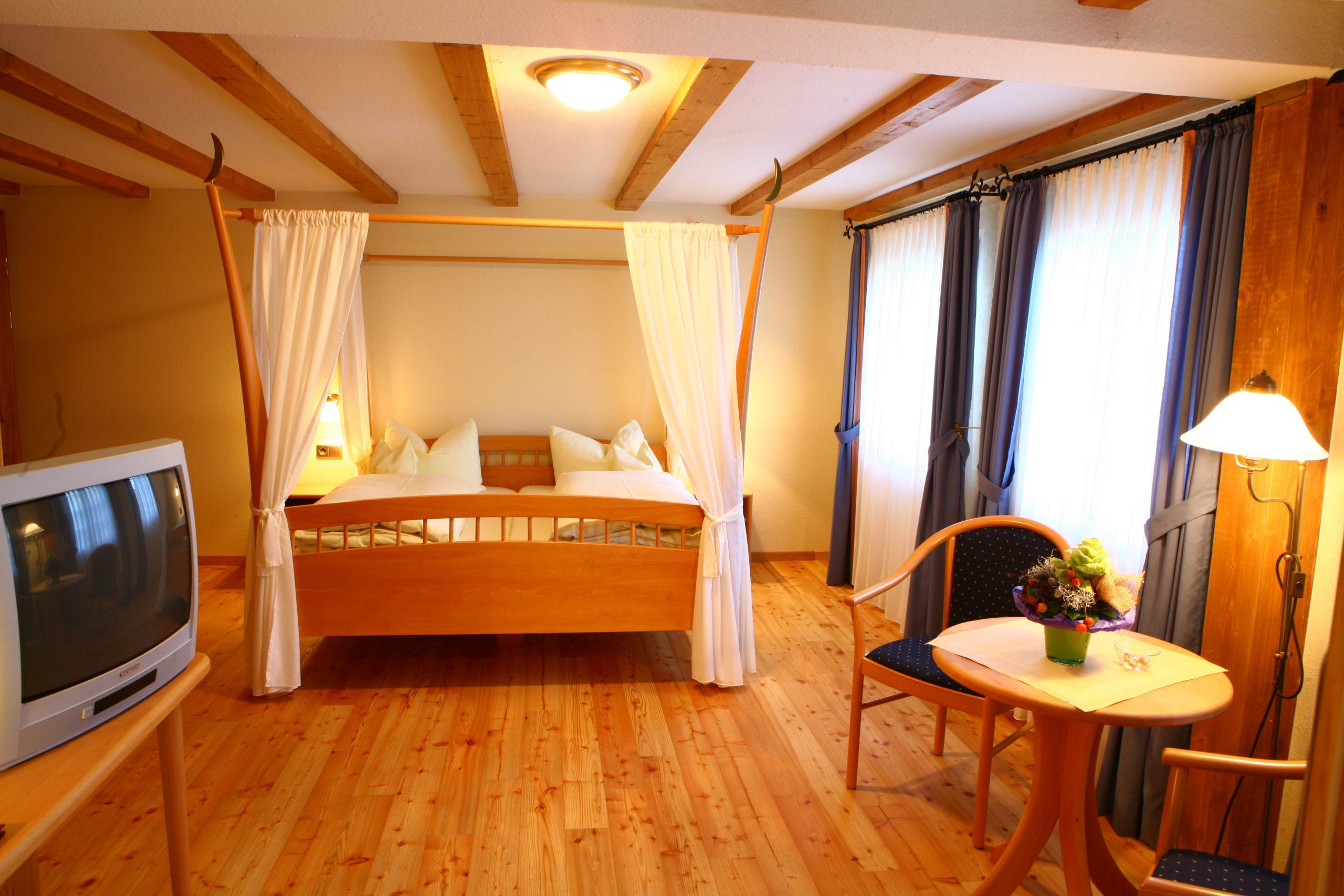 Ein Doppelzimmer komfort: Holzboden, in der Mitte ein Himmelbett aus Holz, links ein Fernsehgerät, recht eine Sitgelegenheit und zwei Fenster mit bodenlangen Vorhängen, warmes Licht.