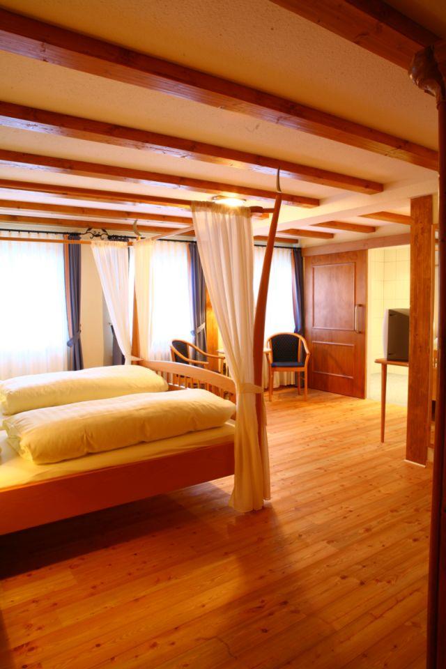 Ein Doppelzimmer komfort: Holzboden, ein Himmelbett aus Holz mit weißen Vorhängen, warmes Licht und helle Gardinen schaffen sorgen zusätzlich für Gemütlichkeit.