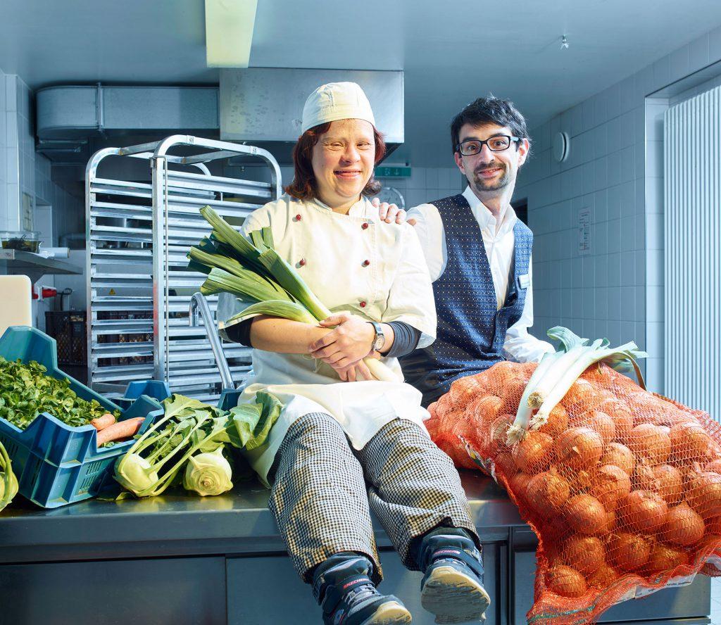 In der Küche des Hofguts. Eine Mitarbeiterin aus der Küche und ein Kellner sitzen lachend auf einer Anrichte. Beide sind von frischem Gemüse umgeben. Grüne Bohnen, Kohlrabi, ein großer Sack Zwiebeln und in ihrem Arm mehrere Stangen Lauch.
