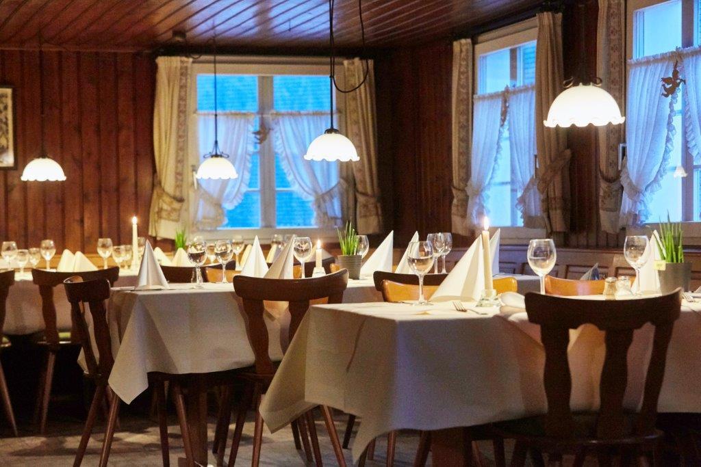 Die festlich gedeckte Gaststube mit Holzvertäfelung an der Wand und Lampenschirmen, die für warmes Licht sorgen. Hinter den Fenstern dämert es allmählich.