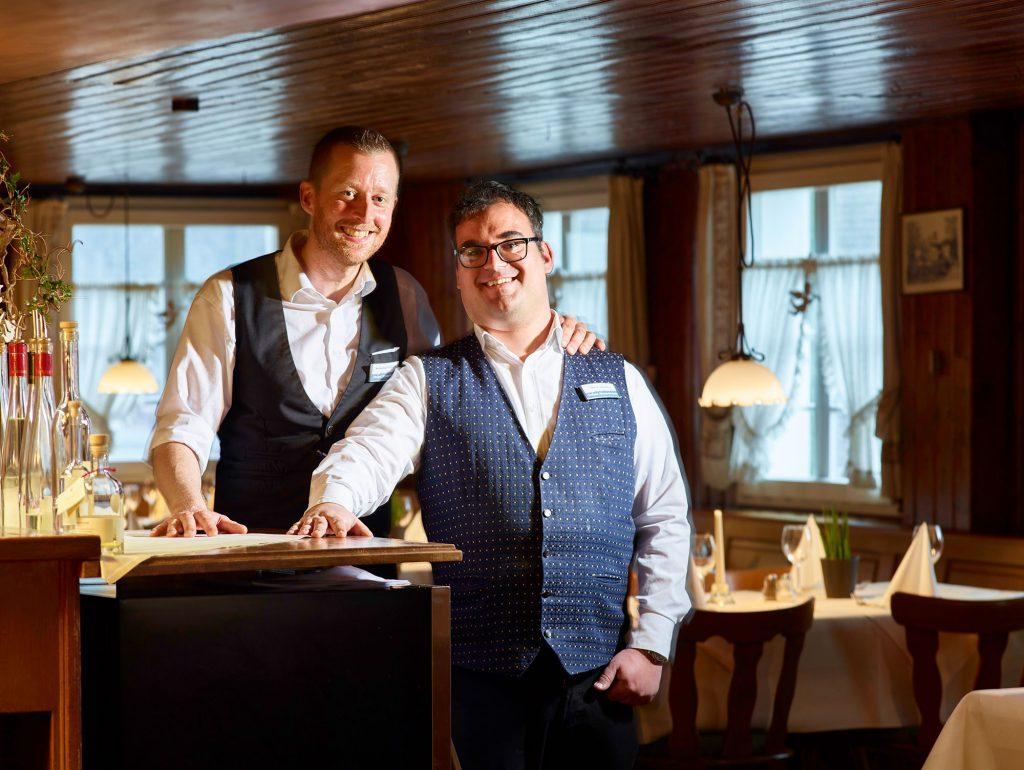 Die Kellner Sebastian Gerhard und Max Grässlin stehen im Gastraum an der Theke und lachen in die Kamera.