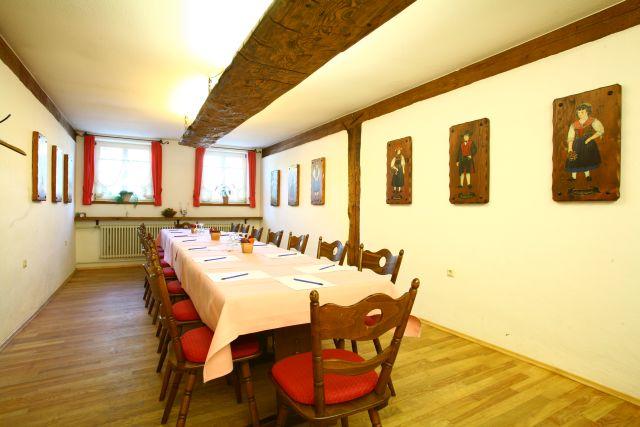 Die Trachtenstube: Tagungsraum mit einem langen Tisch und zwei Fenstern am Ende.