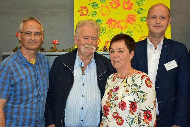 Vier Personen bei einem besondern Anlass: Der frühere Geschäftführer Jürgen Dangl, die inzwischen pensonierte Mitarbeiterin Monika Pollmann und zwei weitere Herren blicken in die Kamera. nner und Monika Pollmann blicken in die Kamera.