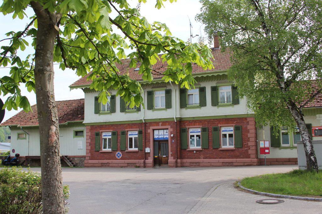 Die Akademie Himmelreich: Ein denkmalgeschütztes Bahnhofsgebäude mit grünen Fensterläden. Die Fenster im Erdgeschoss zeigen alle das Logo der Akademie. Vor dem Gebäude ein großer Platz, Bäume und Grünflächen.