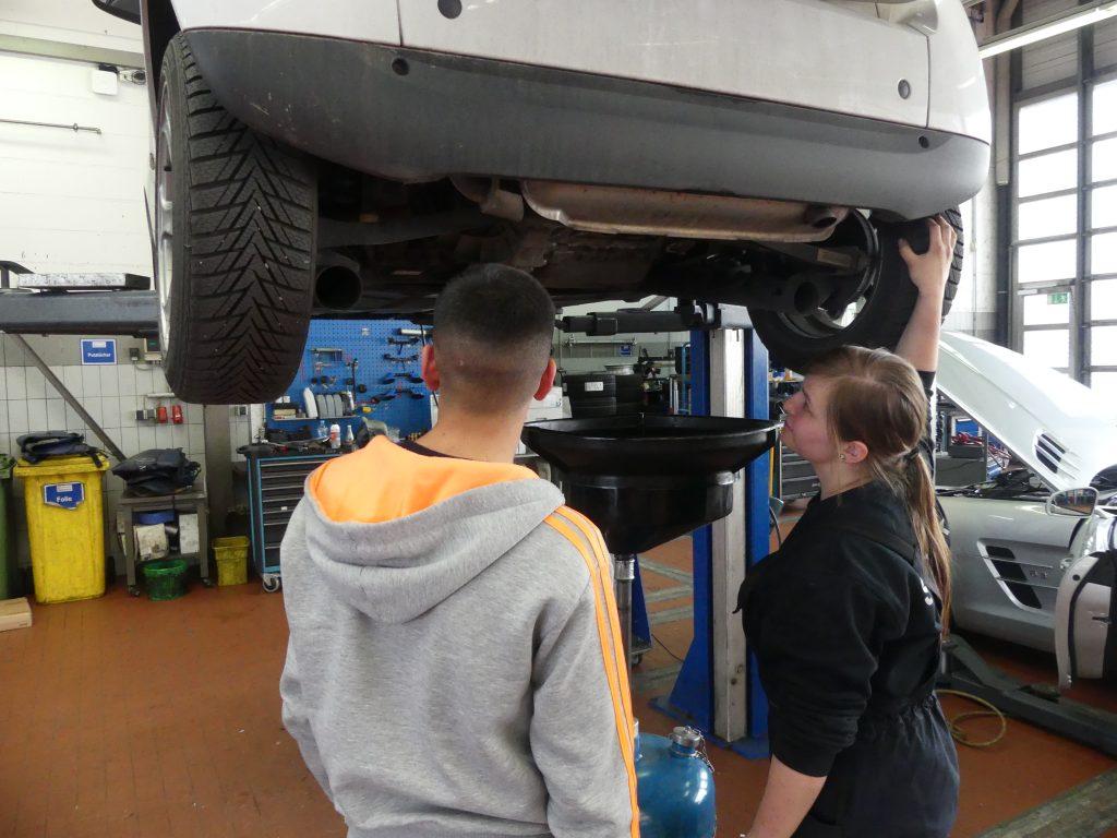 Praktikum in der Autowerkstatt. Praktikant und Auszubildende stehen unter einem Auto auf der Hebebühne.