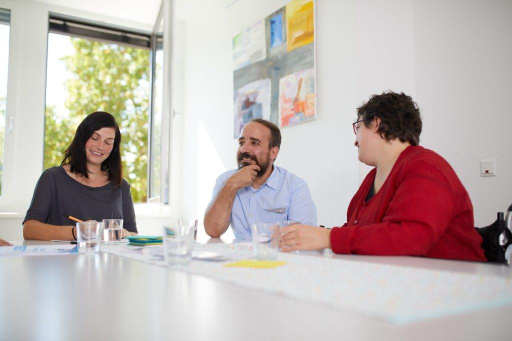 Besprechung zu dritt. Die Beraterinnen Dominika Röderer und Melanie Hildmann sowie ein Klient.