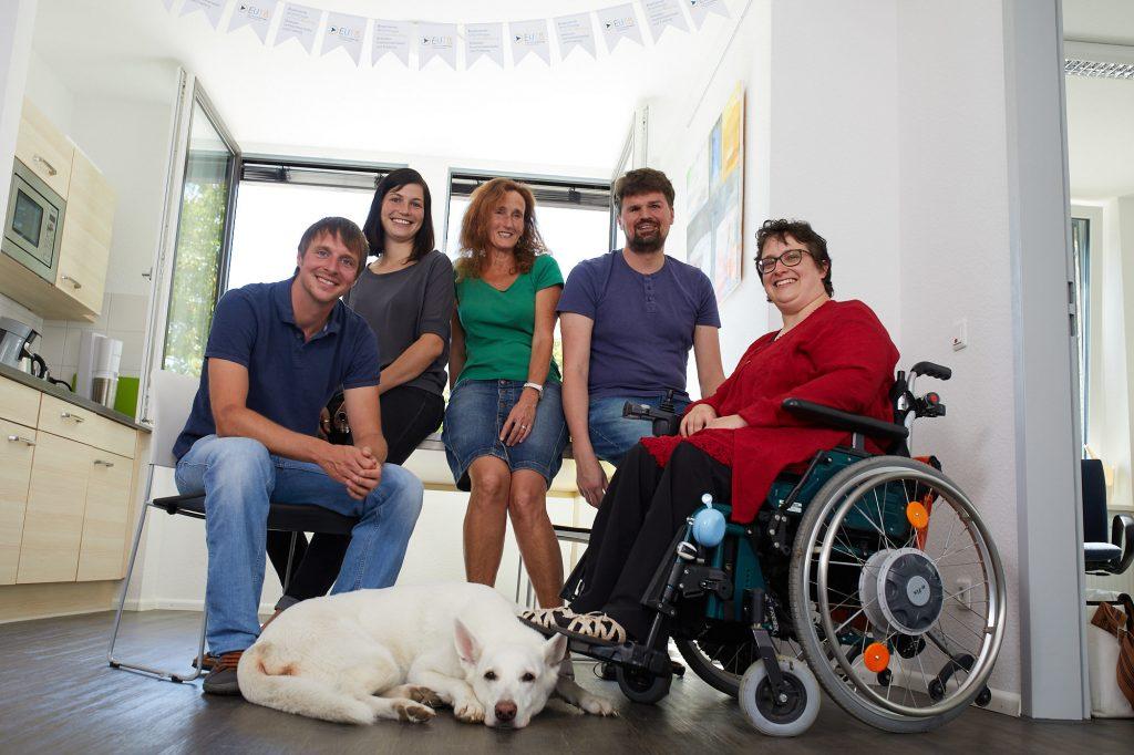 Das Berater*innen-Team. Mathias Schulz, Dominika Rödig, Silvia Geisslreither, Ramon Kathrein, Melanie Hildmann und die Blindenhündin Juli. Auch ein Rollstuhl ist vertreten.