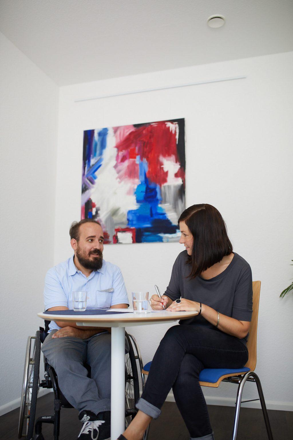 Beratungssituation an einem kleinen Besprechungstisch. Die Beraterin Dominika Rödig und eine Person mit Rollstuhl.