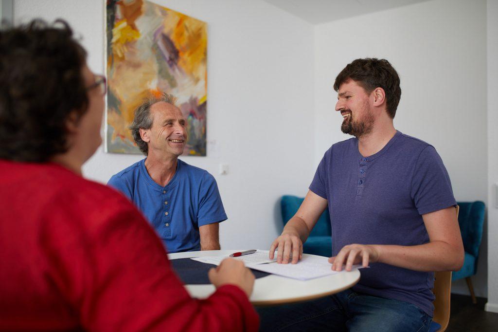 Ein Beratungssituation. Drei Personen um einen runden Tisch. Der Berater Ramon Kathrein liest Brailleschrift.