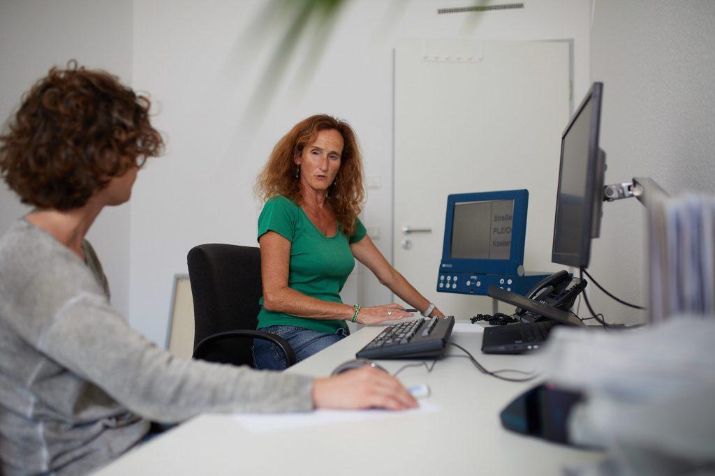 Die Beraterin Silvia Geisslreither vor PC und Lesegerät mit einer Frau am Schreibtisch