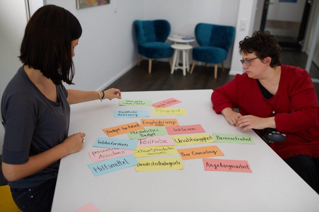 Die Beraterinnen Dominika Rödig und Melanie Hildmann an einem Tisch. Auf dem Tisch viele Moderationskarten mit Begriffen wie
