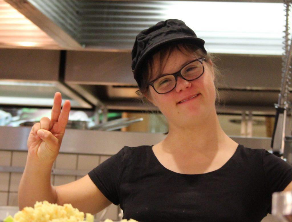 Eine junge Frau mit Down-Syndrom steht in einer Restaurantküche, trägt das dort übliche Outfit mit schwarzer Schildkappe und schwarzem Shirt. Sie reckt Zeige- und Mittelfinger in die Luft und lacht.