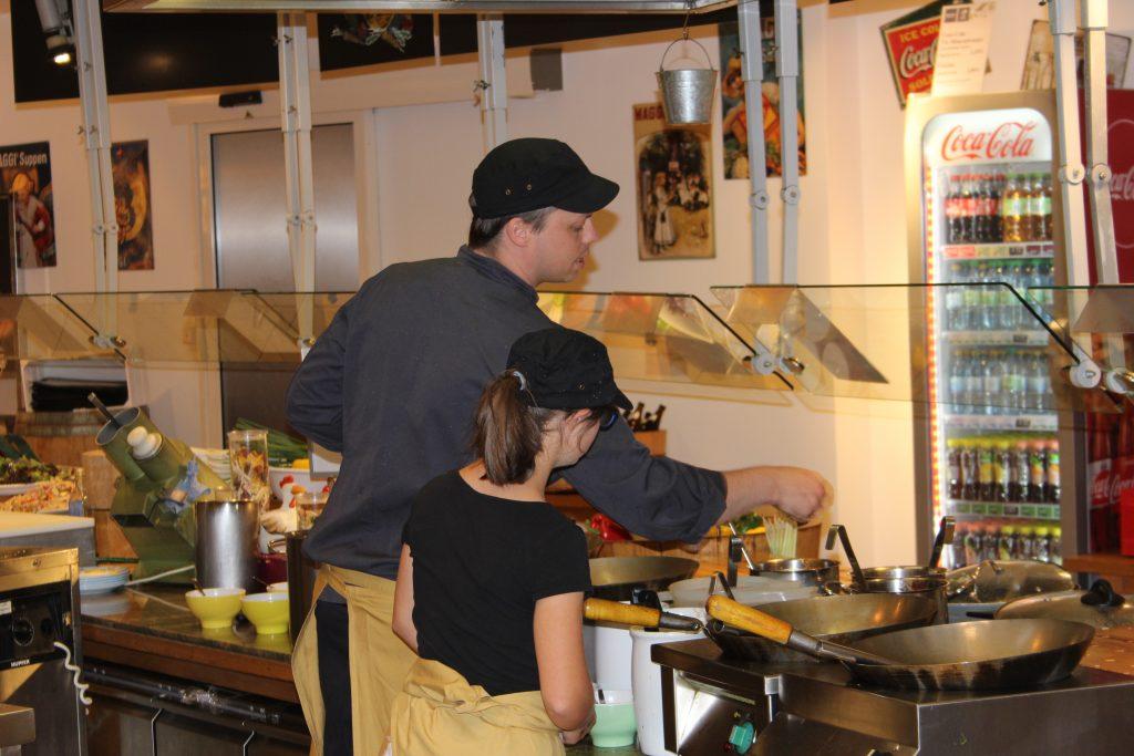 Praktikum in einer Restauranküche. Praktikantin und Azubi sind von hinten zu sehen. Sie stehen gemeinsam am Herd.