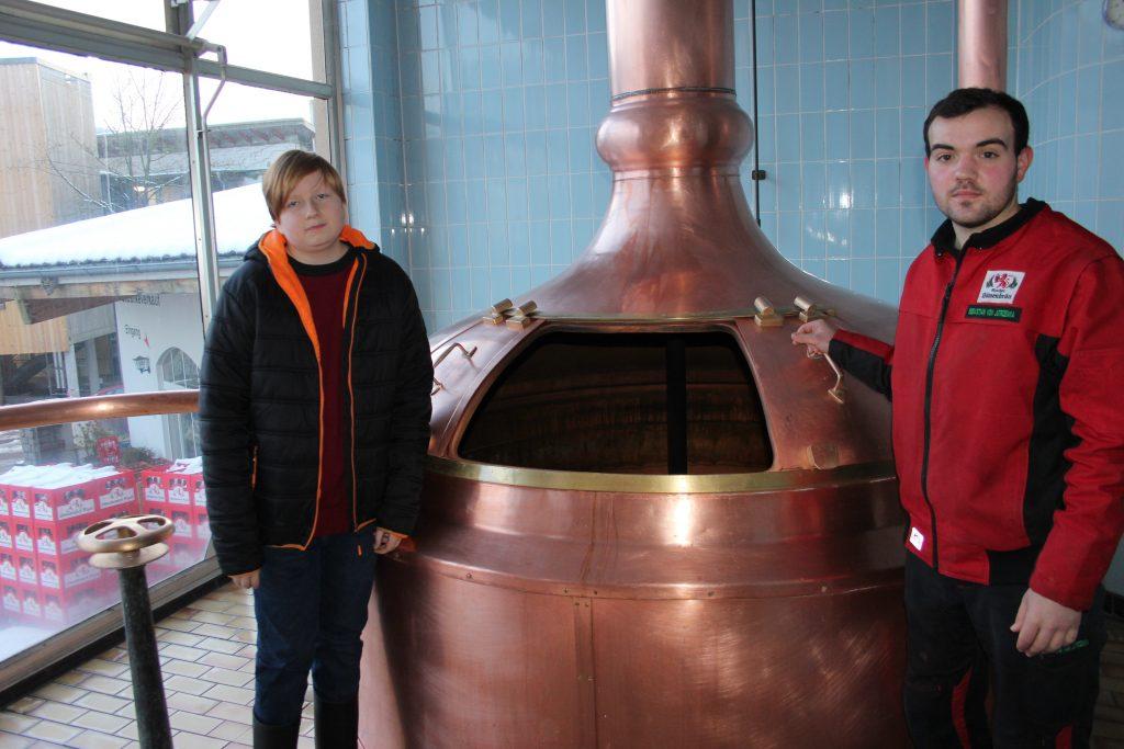 Praktikum in einer Brauerei. Praktikant und Azubi stehen vor einem großen Kupferkessel.