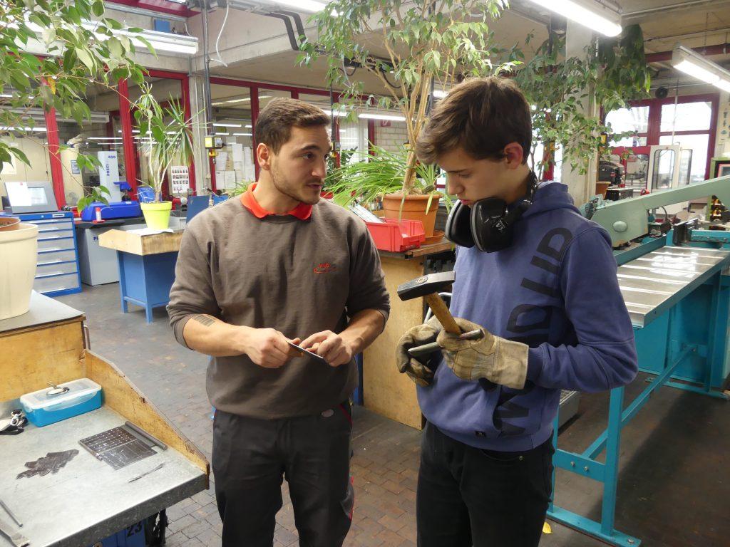 Praktikum bei der VAG Freiburg. Praktikant und Azubi stehen im Werkraum und besprechen den nächsten Arbeitsschritt.