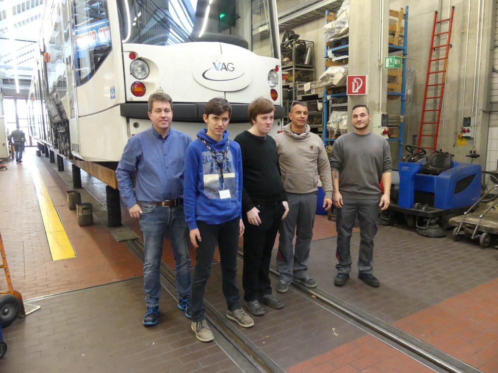 Praktikum bei der VAG Freiburg: Zwei Schüler, zwei Auszubildende und deren Ausbilder stehen in der Werkstatt vor einer Straßenbahn.