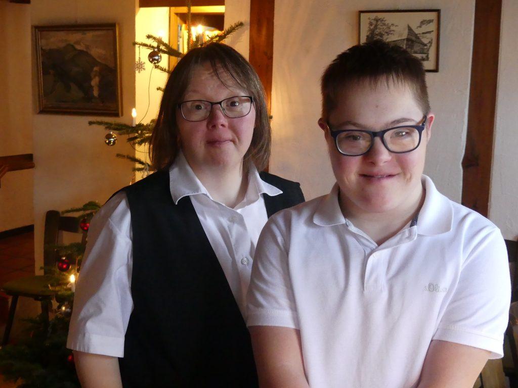 Praktikum im Restaurant. Praktikant und Anleiterin, beide mit Down-Syndrom, lachen in die Kamera.