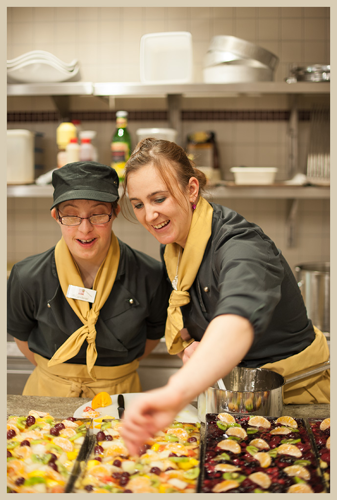 Ein Teilnehmerin und ihre Anleiterin im Küchen-Outfit bestücken gemeinsam Blechkuchen mit Obst und lachen dabei.