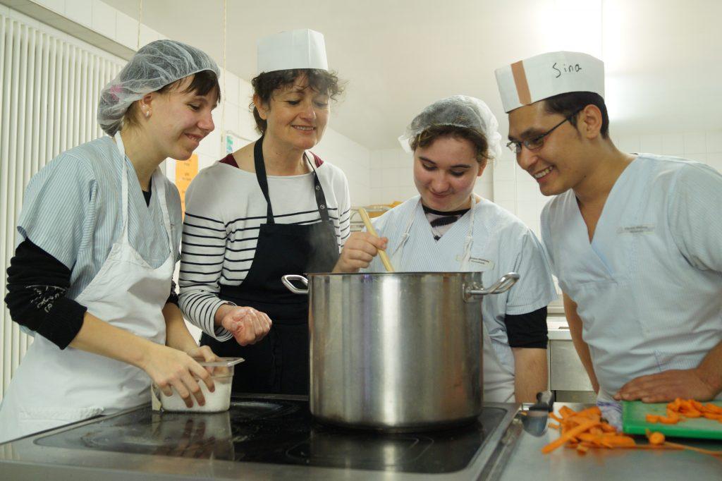 Drei Teilnehmende und eine Anleiterin, alle mit Schürzen und Kochmütze, blicken in einen großen Kochtopf und lachen.