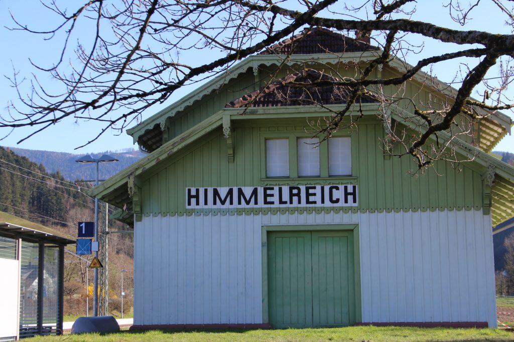 Die Rückseite des denkmalgeschützen Bahnhofsgebäudes. Weiße Hauswand, Holzvertäfelung im Giebel und das große Holztor in der Mitte sind mintgrün. In großen Lettern ist die Haltestelle