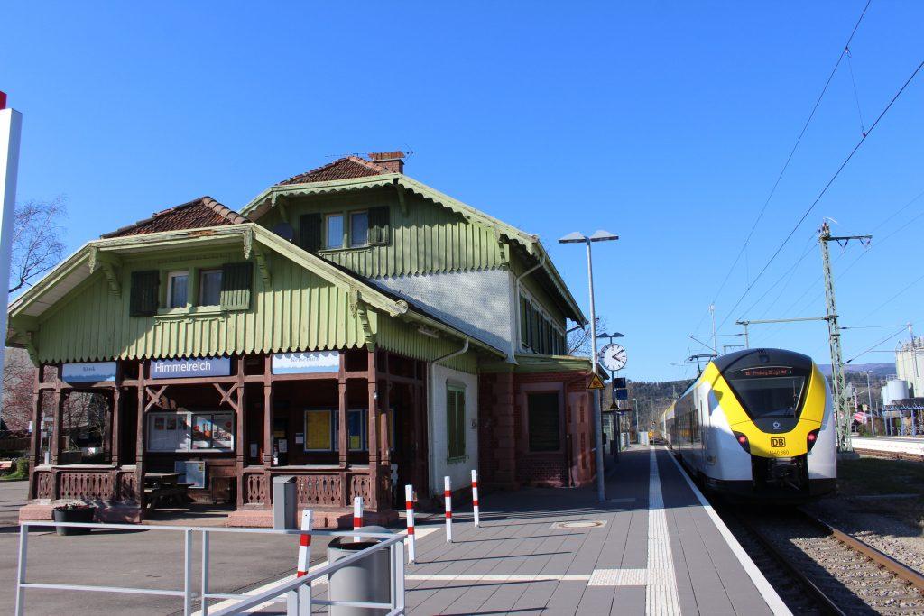 Blick vom Bahnsteig aus auf das denkmalgeschützte Bahnhofsgebäude. Auf dem Gleis steht gerade die Breisgau S-Bahn