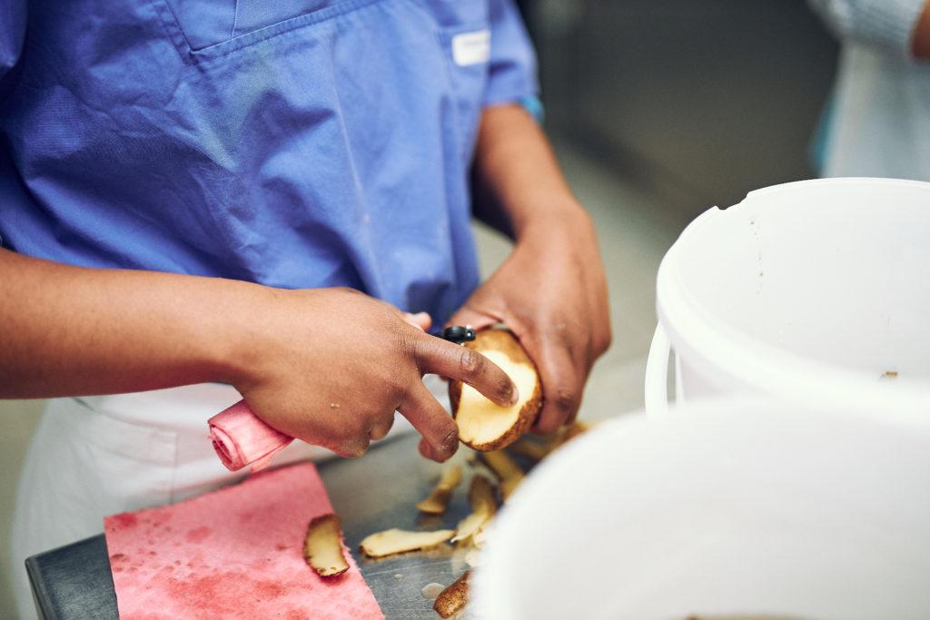 Blick auf zwei Hände, die eine Kartoffel schälen