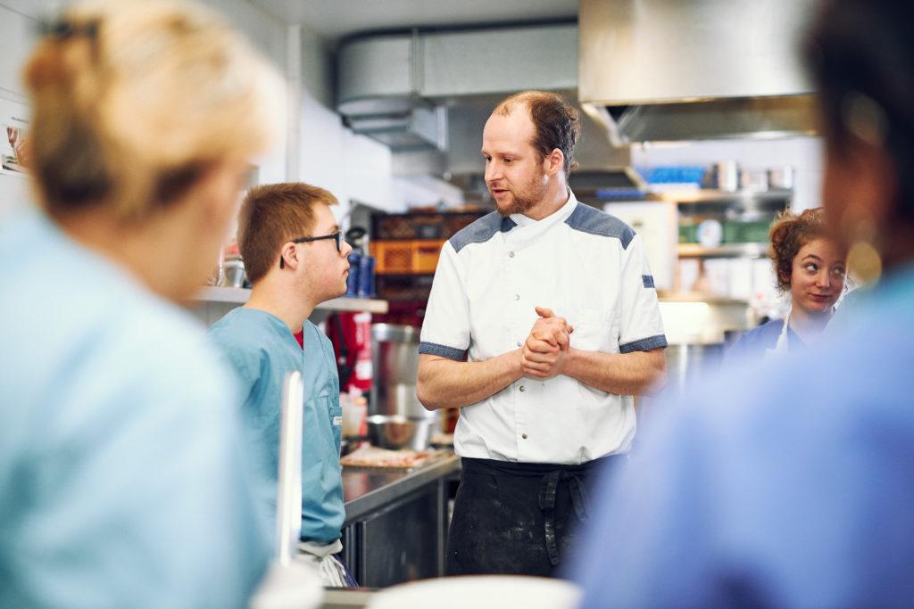 Lehrkoch Marc Diehm in der Lehrküche umringt von Teilnehmenden erklärt den nächsten Arbeitsschritt